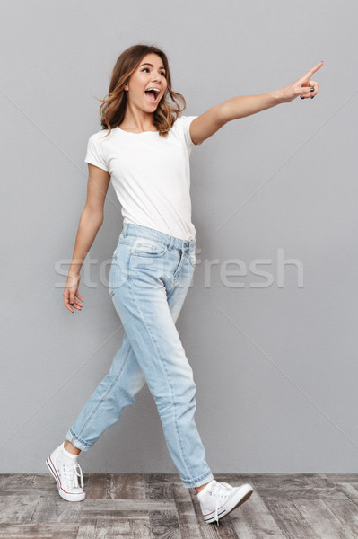 Full length portrait of a happy young woman Stock photo © deandrobot