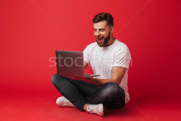 Megrémült mosolyog fiatalember ül izolált laptopot használ Stock fotó © deandrobot