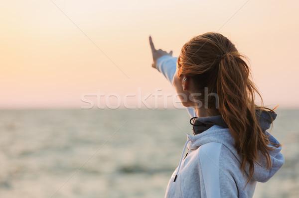 Fiatal lány sportruha mutat víz áll tengerpart Stock fotó © deandrobot