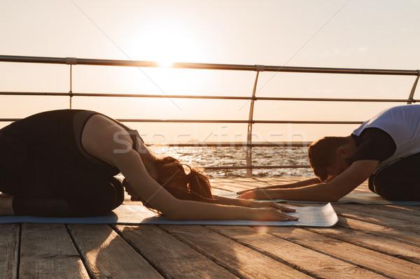Nyugodt fiatal sportok pár gyakorol jóga Stock fotó © deandrobot