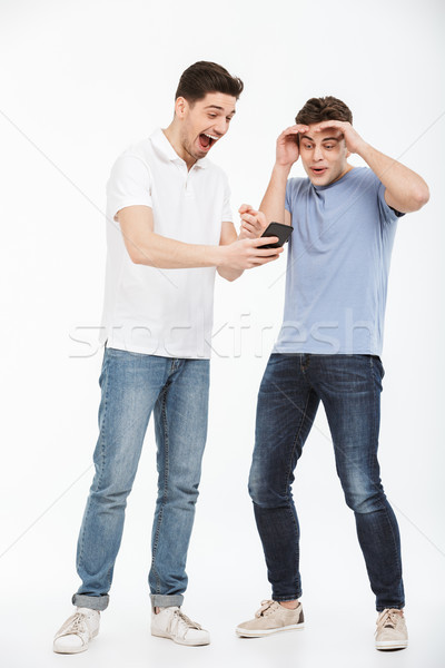Full length portrait of two surprised young men Stock photo © deandrobot