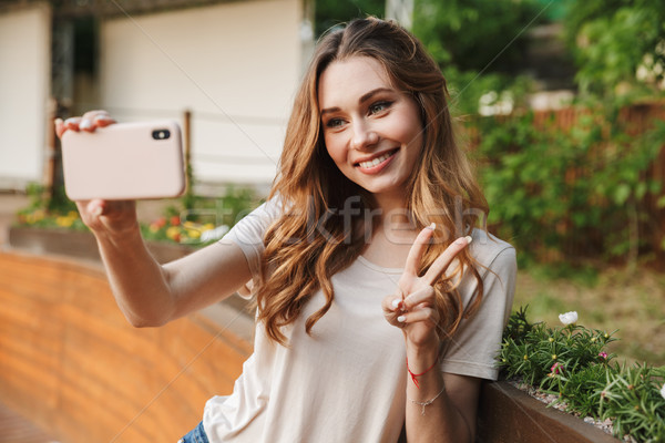 Smiling young girl in casual clothes taking selfie Stock photo © deandrobot