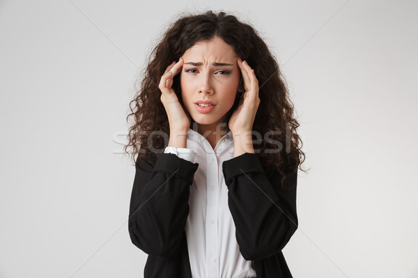 Displeased young business woman with headache Stock photo © deandrobot