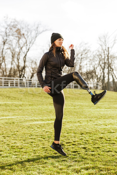 Image of energetic handicapped sportswoman in tracksuit, warming Stock photo © deandrobot