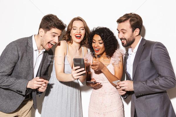 Csoport boldog jólöltözött emberek néz mobiltelefon Stock fotó © deandrobot