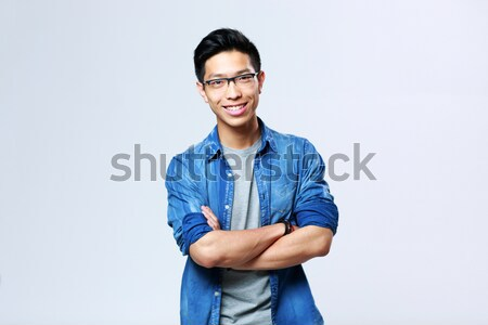 Portrait of a young cheerful asian man with arms folded on gray background Stock photo © deandrobot