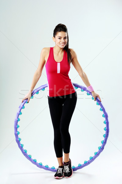 Young smiling sport woman holding a massage hoop on gray background Stock photo © deandrobot
