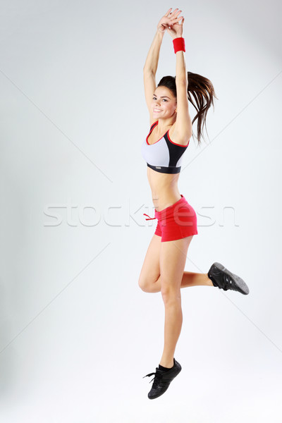 Full-length portrait of a young smiling sport woman jumping on gray background Stock photo © deandrobot