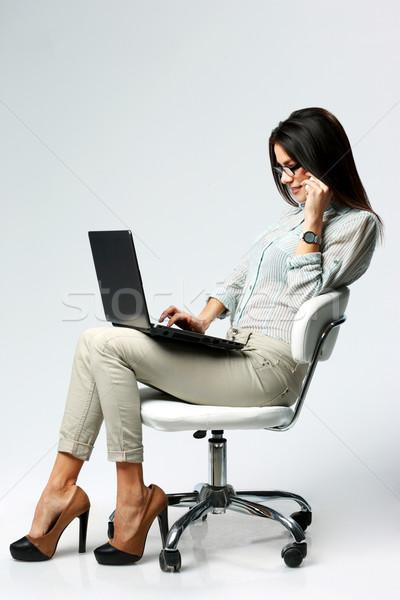 Stock fotó: Fiatal · gyönyörű · üzletasszony · laptopot · használ · beszél · telefon