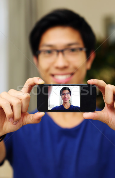 Smiling asian man taking self picture with smartphone camera. Focus on smartphone Stock photo © deandrobot