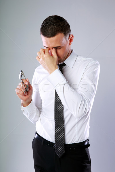 Stock photo: Portrait of a businessman holding glasses and rubbing his eyes on gray background