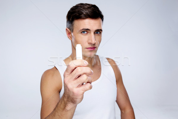 Portrait of a man holding lipstick over gray background Stock photo © deandrobot