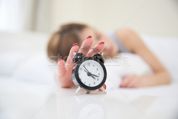 Sleepy woman in bed switching off alarm clock. Focus on clock Stock photo © deandrobot