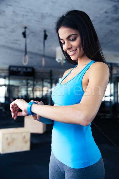 Smiling young woman using activity tracker Stock photo © deandrobot