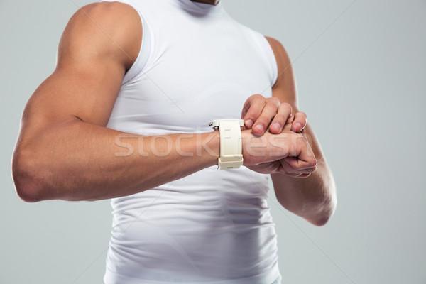 Closeup portrait of a muscular man using smartwatch Stock photo © deandrobot