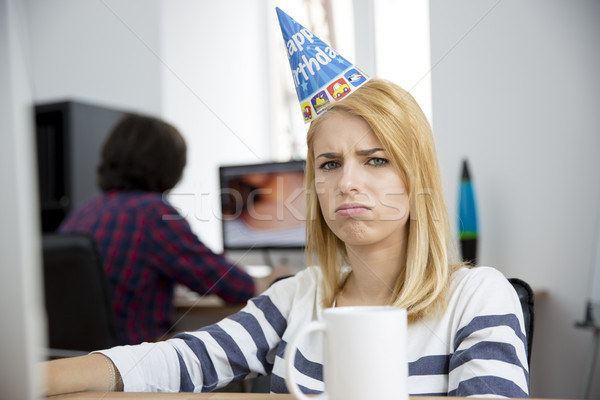 Sad woman with birthday hat sitting at the table Stock photo © deandrobot