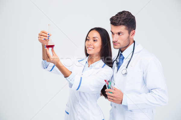 Two medical workers looking at tube with liquid  Stock photo © deandrobot
