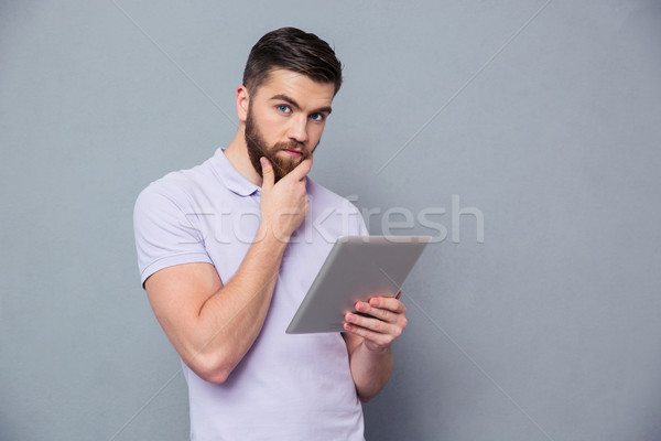 Thoughtful man holding tablet computer Stock photo © deandrobot