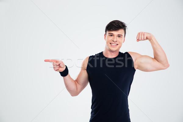 Gelukkig man tonen biceps wijzend vinger Stockfoto © deandrobot