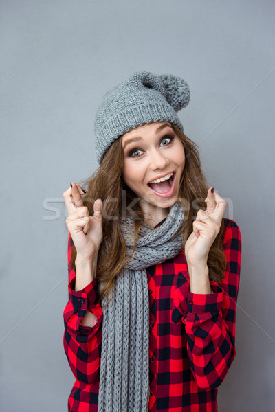Amusing girl in scarf and hat smiling with crossed fingers Stock photo © deandrobot