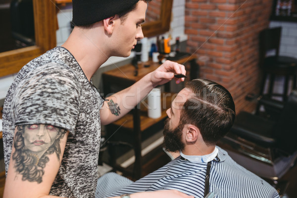 Young hairstylist combing hair of male client with comb Stock photo © deandrobot
