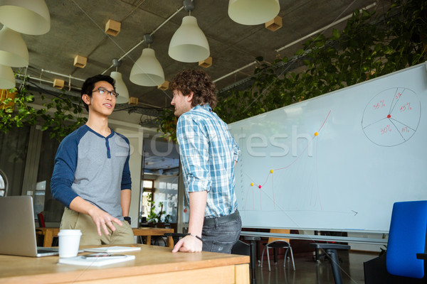 Confident male students standing and talking in classroom Stock photo © deandrobot