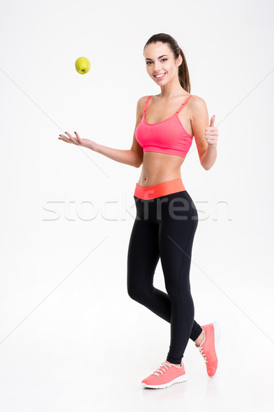 Cheerful fitness woman throwing an apple and showing thumbs up Stock photo © deandrobot