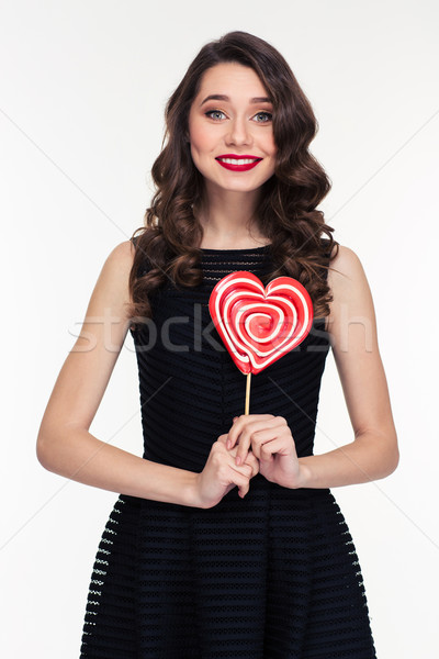 Beautiful happy curly retro styled woman holding heart shaped lollipop Stock photo © deandrobot