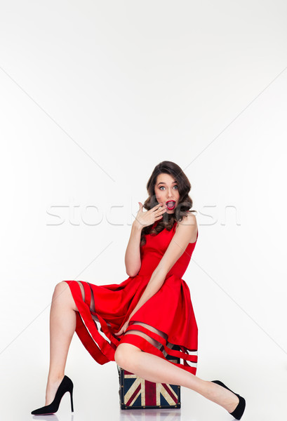 Relaxed shocked curly retro styled woman sitting on vintage suitcase Stock photo © deandrobot