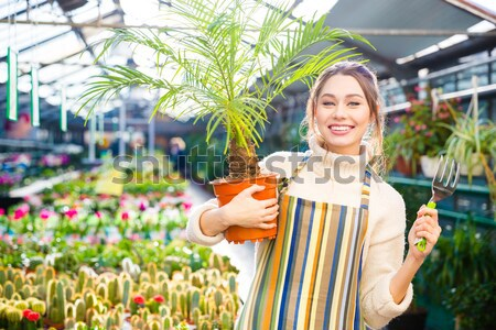 Happy woman gardener holding garden shovel and watering can  Stock photo © deandrobot