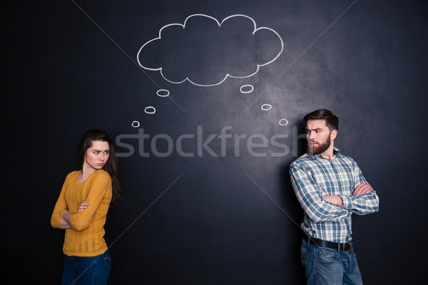 Frowning angry couple thinking identically over background of chalkboard Stock photo © deandrobot