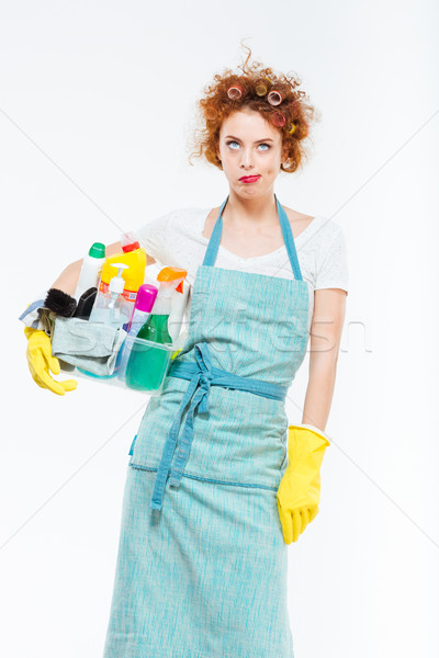 Irritated woman in yellow gloves holding box with cleansers  Stock photo © deandrobot