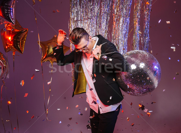 Happy man holding disco ball and dancing alone  Stock photo © deandrobot