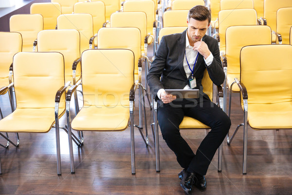 Businessman working with tablet in conference hall  Stock photo © deandrobot