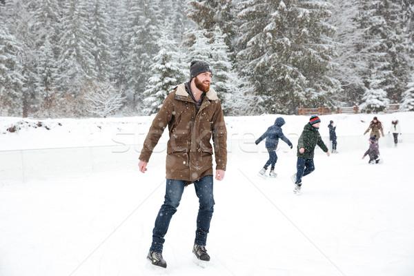 Happy man ice skating outdoors Stock photo © deandrobot