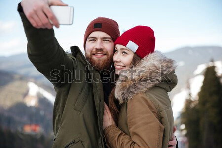 Happy couple using smartphone together in winter Stock photo © deandrobot
