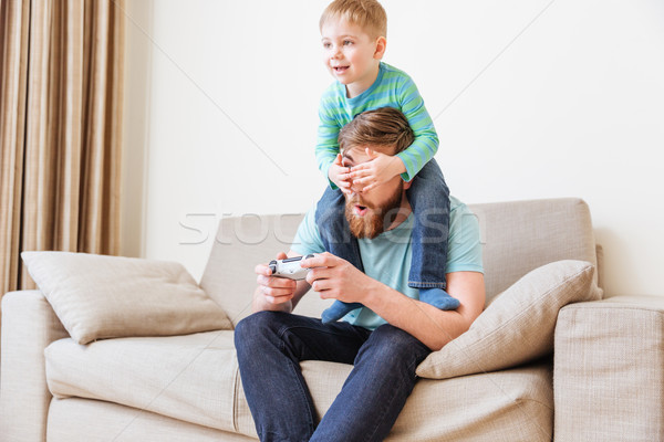 Little boy covering father eyes while he playing computer games Stock photo © deandrobot