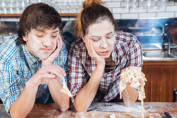 Sad bored couple with flour on faces kneading dough Stock photo © deandrobot