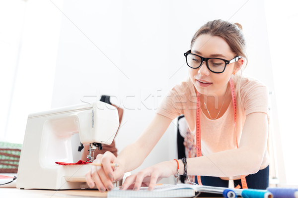 Concentrated woman seamstress wearing glasses standing and working in workshop Stock photo © deandrobot
