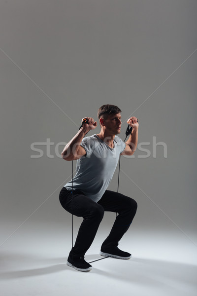 Fitness man squatting with expander Stock photo © deandrobot