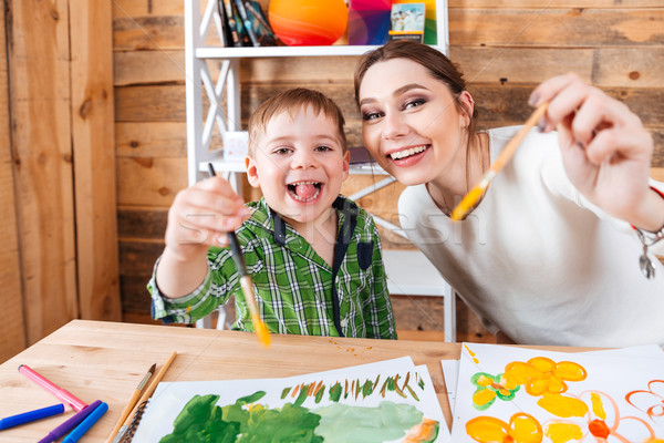 Cheerful little boy and his mother showing paintbrushes to camera  Stock photo © deandrobot