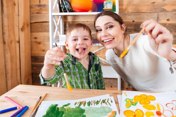 Derűs kicsi fiú anya mutat festőecsetek Stock fotó © deandrobot