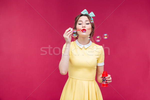 Attractive pinup girl in yellow dress blowing soap bubbles Stock photo © deandrobot