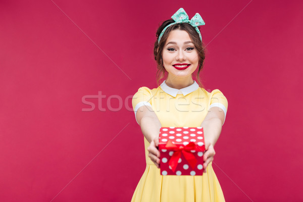 Smiling beautiful young woman giving you a present in box Stock photo © deandrobot