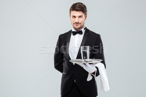 Butler in gloves holding glass of water on silver tray Stock photo © deandrobot