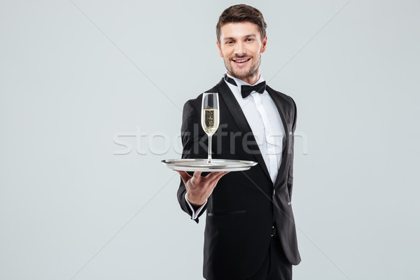 Cheerful butler in tuxedo offering you glass of champagne Stock photo © deandrobot