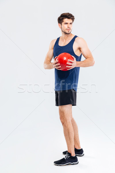 Serious young sportsman standing and exercising witn red ball Stock photo © deandrobot