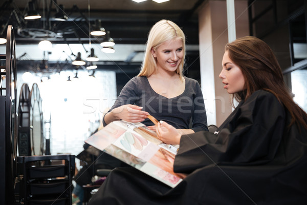 Woman with hairdresser choosing hair color from palette at salon Stock photo © deandrobot