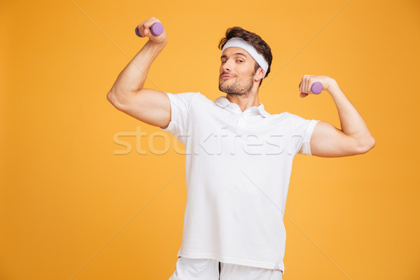 Smiling young sportsman standing and posing with dumbbells Stock photo © deandrobot