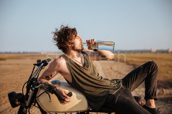 Fiatal brutális férfi fektet motorkerékpár ivóvíz Stock fotó © deandrobot
